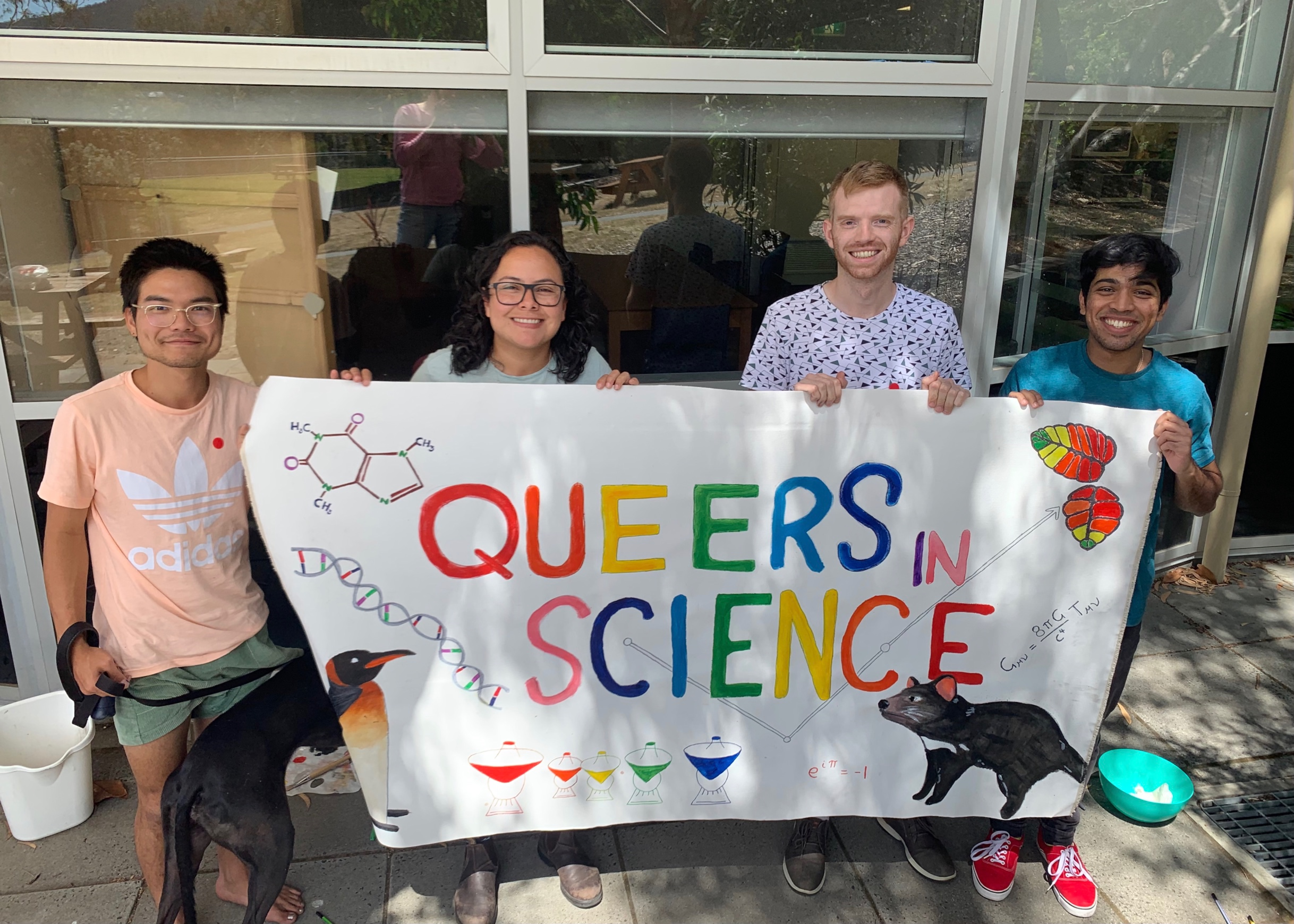 Ink, Petra, Ross and Zach holding to QueersInScience banner.